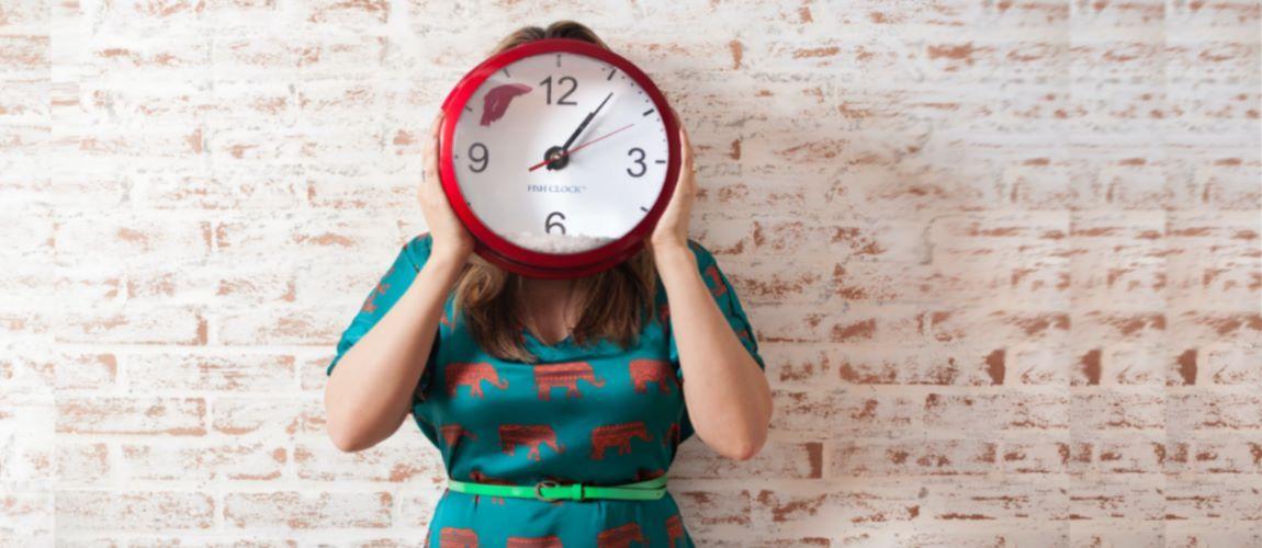 Frau hält Uhr vor Gesicht