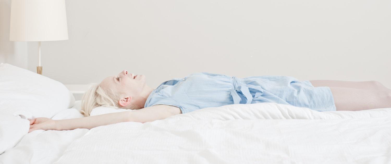 Frau liegt bequem auf Bett
