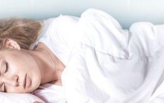 Frau schläft im Bett mit Funktionsmaterialien